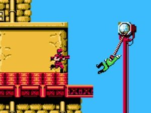 Side scrolling perspective from Bionic Commando where the player is using his bionic arm to swing from a lamppost away from an enemy